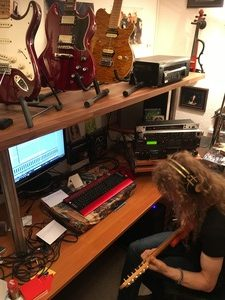 Tommy working, with guitars on shelf